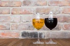 röd vit wine för exponeringsglas Exponeringsglas för rött och vitt vin på en gammal tegelstenvägg Arkivbild