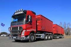Röd Volvo FH lastbil med den fulla släpet och blå himmel Arkivbild
