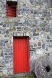 Röd wood dörr och fönster i ursnygg stenbyggnad Royaltyfri Foto