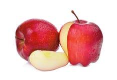 Röda äpplen för helhet och för skivor med vattendroppar som isoleras på vit fotografering för bildbyråer