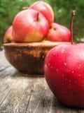 Röda äpplen i en lergodshandfat på en gammal trätabell fotografering för bildbyråer