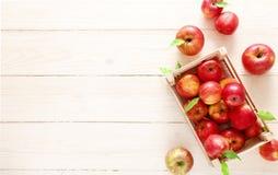 Röda äpplen i en ljus träask Royaltyfri Bild