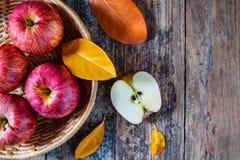 Röda äpplen i korg på gammalt en trätabell royaltyfria foton