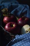 Röda äpplen i korgen med denblått torkduken royaltyfria foton