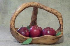 Röda äpplen i träkorg på naturligt plundra material Arkivbild