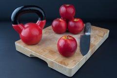 Röda äpplen, kniv och kettlebell på skärbräda Arkivbilder