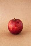 Röda äpplen på bakgrund för brunt papper Arkivfoto