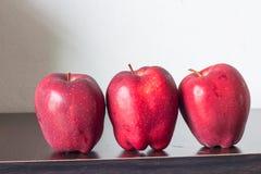 Röda äpplen på bordlägga Arkivbilder