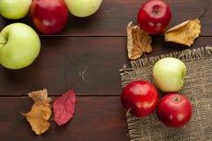 Röda äpplen på den lantliga trätabellen Arkivfoton