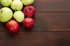 Röda äpplen på den lantliga trätabellen Arkivbilder