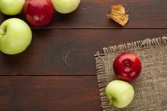 Röda äpplen på den lantliga trätabellen Royaltyfri Bild