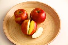 Röda äpplen på en träplatta på tabellen Royaltyfria Foton