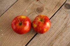 Röda äpplen på en träplatta på tabellen Arkivfoton