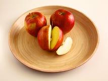 Röda äpplen på en träplatta på tabellen Royaltyfria Bilder