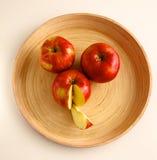 Röda äpplen på en träplatta på tabellen Royaltyfri Foto