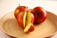 Röda äpplen på en träplatta på tabellen Arkivfoto