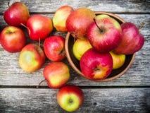 Röda äpplen på en trätabell arkivbild