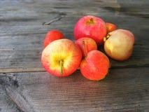 Röda äpplen på en träyttersida Arkivbild