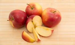 Röda äpplen på servicefärg av ett träd Arkivfoto