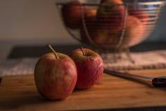Röda äpplen på skärbräda Arkivfoto
