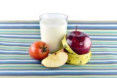 Röda äpplen som mäter bandet, exponeringsglas av, mjölkar och tomaten in på naper Royaltyfria Foton