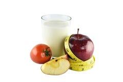 Röda äpplen som mäter bandet, exponeringsglas av, mjölkar och tomaten på vita lodisar Arkivbilder