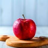 Röda Apple på det wood brädet Fotografering för Bildbyråer