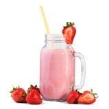 Röda bär ligger framme av en glass krus som fylls med den naturliga smoothien med ett färgrikt sugrör som isoleras på en vit bakg Royaltyfri Bild