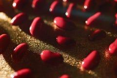 Röda bönor ligger på en guld- bakgrund i defocusen Royaltyfri Fotografi