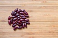 Röda bönor på det wood golvet arkivbild