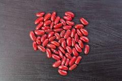 Röda bönor på träbakgrunder Fotografering för Bildbyråer