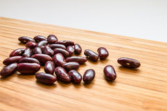 Röda bönor på trät fotografering för bildbyråer