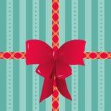 Röda band och pilbåge som binds på randigt gåvainpackningspapper Royaltyfri Bild