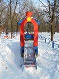 Röda barns glidbana som en lokomotiv i snön parkerar område av ‹för †staden Arkivbilder