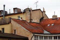 Röda belade med tegel tak, väggarna av hus och lampglas Royaltyfri Bild