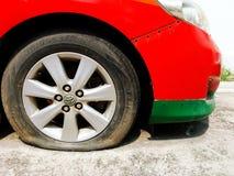 Röda bilparkering som, är brutna och, stänger sig upp det plana gummihjulet för bilen på gatan royaltyfri foto