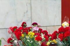 Röda blommor ligger på foten av monumentet av stenen Arkivfoton