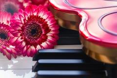 Röda blommor och ask av choklader på ett pianotangentbord arkivfoton