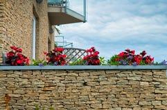 Röda blommor på en balkong Arkivbilder