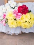 Röda blommor på tabellen av blommaordningen Arkivfoto