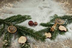 Röda bollar, grangräsplan och snö med deco Arkivbilder