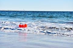 Röda bollar på våghavstranden Arkivbilder