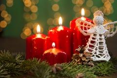 Röda brinnande adventstearinljus med virkningängel och sörjer trädstilleben Arkivfoto
