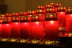Röda burning stearinljus inom en kyrka Royaltyfria Foton