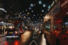 Röda bussar för dubbel däckare, svarta taxiar och bilar på den Oxford gatan, London som dekoreras med julljus royaltyfri foto