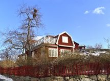 Röda charmiga trähus i Vaxholm med vitklippning, en veranda är också ovanför den glasade förlängningen Fotografering för Bildbyråer