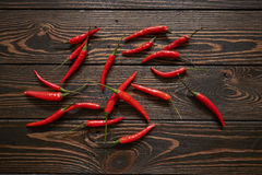 Röda chili på wood bakgrund Royaltyfri Bild
