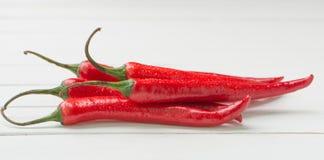 Röda Chili Peppers över vit tabellbakgrund Arkivbilder