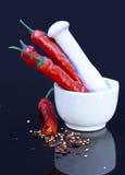 Röda chilipeppar i mortel Fotografering för Bildbyråer