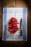 Röda chilipeppar med kniven Arkivbild